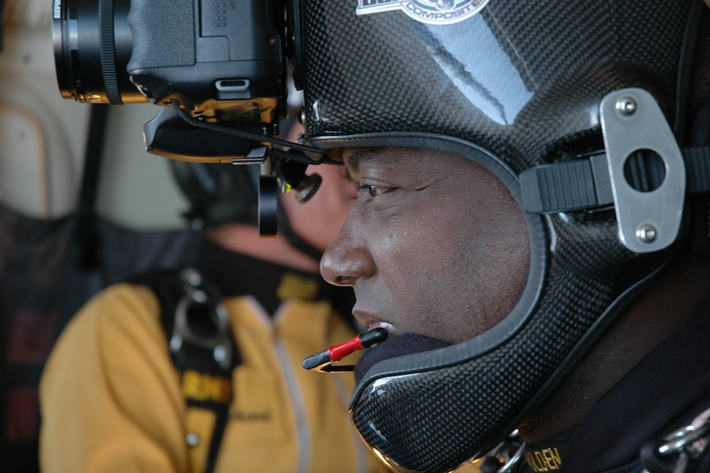 "OVER EGLIN AIR FORCE BASE, Fla. -- U.S Army Staff Sgt. Marc Owens, U.S. Army Parachute Team ""Golden Knights"" aerial demonstration team freefall videographer, watches as fellow members of the team prepare to jump from the C-41 aircraft April 14. Sergeant Owens is wearing a specially designed helmet equipped with a digital camera and a video camera to document the jump over Eglin. The practice show was the only jump the team made due to an April 15 severe weather cancellation of the air show and winds exceeding 20 mph gusts April 16. Sergeant Owens is in his fifth year with the Golden Knights and has made more than 2,000 freefall jumps in his Army career.  (U.S. Air Force photo by Staff Sgt. Mike Meares)"