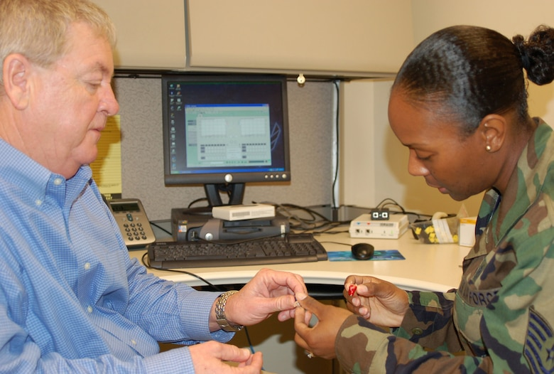 Audiologist Jimmy Pittman shows Tech. Sgt. Nackeesia Holmes a state-of-the-art digital hearing aid in the audiology clinic.  Both are assigned to the 81st Surgical Operations Squadron.  (U.S. Air Force Photo by Steve Pivnick)
