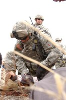 Capt. Joe Peltier, executive officer, intelligence officer and one of the many combat lifesavers for Team 94-07, applies a combat application tourniquet to a civilian on the battlefield during a mass-casualty exercise portion of a group of transition teams' four-day, course-culminating mission-readiness exercise March 22 around Fort Riley's urban clusters. (Photo by Spc. Stephen Baack, 1st Inf. Div. PAO)