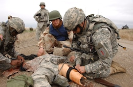 "Maj. Chris Kuhn, battalion team leader for Team 94-07, helps comrades ""save a life"" as he applies a combat application tourniquet to a dummy during the mass-casualty exercise portion of the team's four-day, course-culminating mission-readiness exercise March 22 around Fort Riley's urban clusters.  (Photo by Spc. Stephen Baack, 1st Inf. Div. PAO)"
