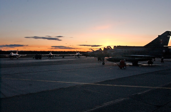 EIELSON AIR FORCE BASE, Alaska--The sun sets on a group of F-16 Fighting Falcons from the 61st Fighter Squadron at Luke AFB, and a French Mirage 2000 sit on the flight line April 16 during Red Flag-Alaska 07-1.  More than 1,300 military members from the United States, France and Australia have gathered in the Last Frontier to participate in Red Flag-Alaska 07-1 scheduled from April 5 to 21. (U.S. Air Force photo by Senior Airman Justin Weaver).