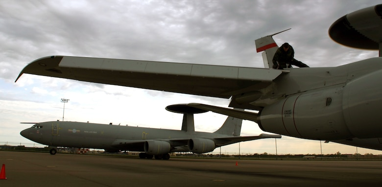 (TINKER AIR FORCE BASE, Okla) An Airman from the 552nd Aircraft Maintenance Squadron conducts post-flight inspections on an E-3B/C Sentry aircraft as its cousin from across the Atlantic - the British E-3D Sentry - taxis to its parking space. Members of the No. 8 Squadron from Royal Air Force Waddington, United Kingdom, conducted a liaison visit to the 552nd Air Control Wing from April 10-17 to open the doors for future mission training and partnership.(Photo by Staff Sgt. Stacy Fowler)