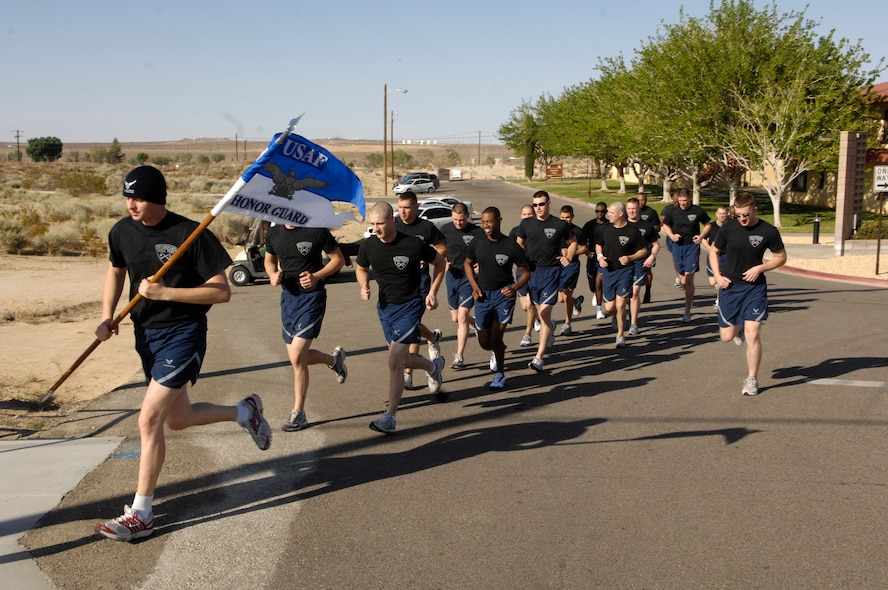Members of the Air Force Honor Guard Drill Team, with guidon in hand, take off for a formation run while visiting at Edwards AFB, Calif. on 18 April 2007.  The Drill Team is the traveling component of the Air Force Honor Guard and tours Air Force bases world wide showcasing the precision of today's Air Force to recruit, retain, and inspire Airmen for the Air Force mission. (U.S. Air Force photo by Senior Airman Daniel R. DeCook)(Released)