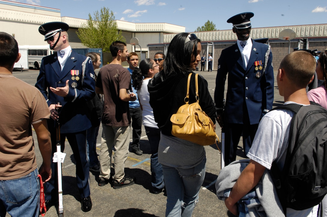 Senior Airmen Timothy Treadway and Jermaine James, Air Force Honor Guard Drill Team members, discuss Air Force opportunities and experiences with students from Lancaster HS, Calif. following their 16 Man performance during their California Tour.  The Drill Team is the traveling component of the Air Force Honor Guard and tours Air Force bases world wide showcasing the precision of today's Air Force to recruit, retain, and inspire Airmen for the Air Force mission.(U.S. Air Force photo by Senior Airman Daniel R. DeCook)(Released)
