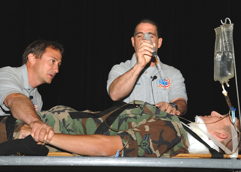 "Mr. Ronny Garcia demonstrates one of the emergency life-saving methods that would be employed after an alcohol-related car accident, while Mr. Vince Easevoli holds down the arms of Airman 1st Class Spencer Doll of the 355th Medical Support Squadron here. Davis-Monthan was one of several stops on the Stay Alive from Education program's ""Street Smart"" demonstration tour, during which Mr. Garcia and Mr. Easevoli educate people on the consequences of poor decision-making. (U.S. Air Force photo/Senior Airman Jacqueline Hawkins)"