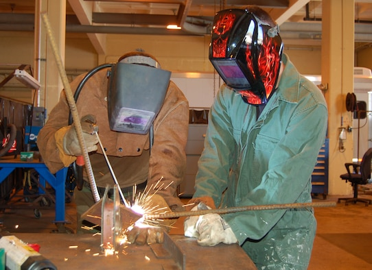 A 554th RED HORSE Squadron member welds an embed for a concrete panel, while a 36th MXS member watches closely. The 554th RED HORSE Squadron and the 36th Maintenance Squadron are working together to accomplish a common goal — the mission. In this particular mission, the 554 RHS needs to use the 36th MXS Metals Technology Shop so they can make metal embeds that will be used for constructing buildings at Northwest Field, the future 554 RHS home. (Photo by Airman Basic Evan Carter/36th Wing Public Affairs)