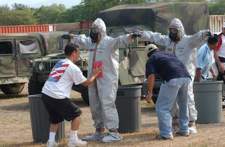 SOTO CANO AIR BASE, Honduras – Abner Radillo (left) from U.S. Aid, and Erling Alvarez, from the U.S. Embassy, process their co-workers through a decontamination line following a major accident response exercise held here April 17-19. Thirty eight students attended the class, which provided training, focusing mainly on first aid techniques, and chemical, biological, radiological, nuclear, and explosive (CBRNE) readiness training, including how to don the chemical protection suit.  (U.S. Air Force photo/Tech. Sgt. Sonny Cohrs)