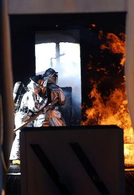 McConnell firefighters extinguish a fire in the cockpit of a mach aircraft, April 11, during a live-fire training exercise on base. Firefighters from the 22nd Civil Engineer Squadron and the Kansas Air National Guard participated in the exercise. (Photo by Airman 1st Class Jessica Lockoski)