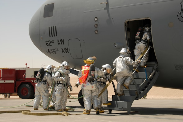 "Firefighters from the 379th Expeditionary Civil Engineer Squadron Fire and Emergency Services Flight practice entering a C-17 Globemaster with the necessary tools and equipment to rescue crewmembers and extinguish an interior fire during an exercise Monday. The hands-on training ensures firefighters are ready to deal with any type of emergency. Firefighters must be proficient in properly shutting-down aircraft engines, activating and discharging the on-board fire suppression system, turning off the ""master"" power switch, and properly opening all emergency exits, doors and windows. (U.S. Air Force photo by Airman 1st Class Gustavo Gonzalez)"
