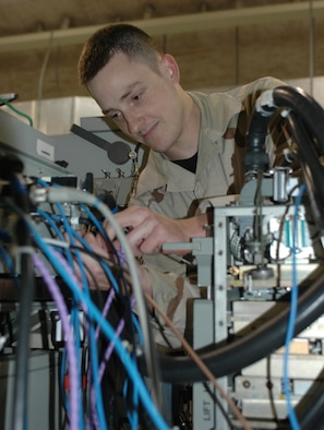 Senior Airman Ryan Burgess, 379th Expeditionary Maintenance Squadron   Avionics Flight team leader, makes adjustments during a radar receiver exciter test.  (U.S. Air Force photo/Staff Sgt. Jasmine Reif)