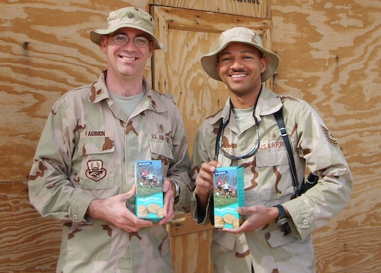 SOUTHWEST ASIA --  Maj. Matthew Faubion and Tech. Sgt. Randall Wallace show their boxes of Girl Scout cookies. The Brownies and Junior Girl Scouts at Osan Air Base sent 636 boxes of Girl Scout cookies to servicemembers deployed to Iraq and Afghanistan. (Courtesy photo)