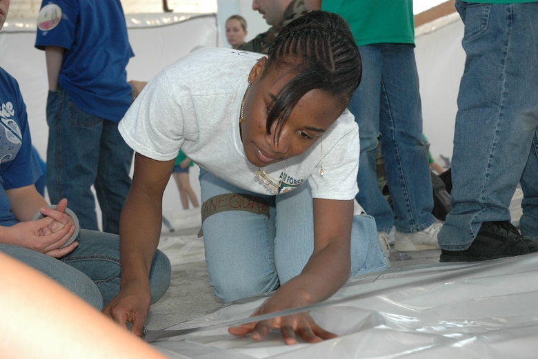 "EGLIN AIR FORCE BASE, Fla. -- Shanequa Hardy, 16,  a Niceville High School Junior Reserve Officer Training Corps cadet, helps to tape a plastic shelter together. Fifth-grade students from three elementary schools kicked off the Marsville Project culminating six weeks of study about space. The project required students from Cherokee, Valparaiso and Longwood Elementary Schools to experience a day of living in ""space"" by building a habitat. During the weeks prior to Marsville, students learned about the life support systems to consider before travel into space, such as the need for air, water, transportation and garbage disposal. Each student built a life support system model to bring with them. (U.S. Air Force photo by Staff Sgt. Mike Meares)"