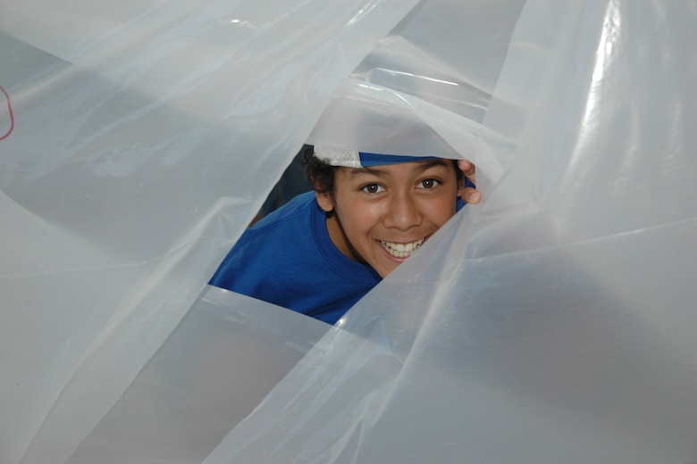 "EGLIN AIR FORCE BASE, Fla. -- Levon Swafford, 11, a fifth grader from Cherokee Elementary School, peeks out of his plastic shelter. Fifth-grade students from three elementary schools kicked off the Marsville Project culminating six weeks of study about space. The project required students from Cherokee, Valparaiso and Longwood Elementary Schools to experience a day of living in ""space"" by building a habitat. During the weeks prior to Marsville, students learned about the life support systems to consider before travel into space, such as the need for air, water, transportation and garbage disposal. Each student built a life support system model to bring with them. (U.S. Air Force photo by Staff Sgt. Mike Meares)"
