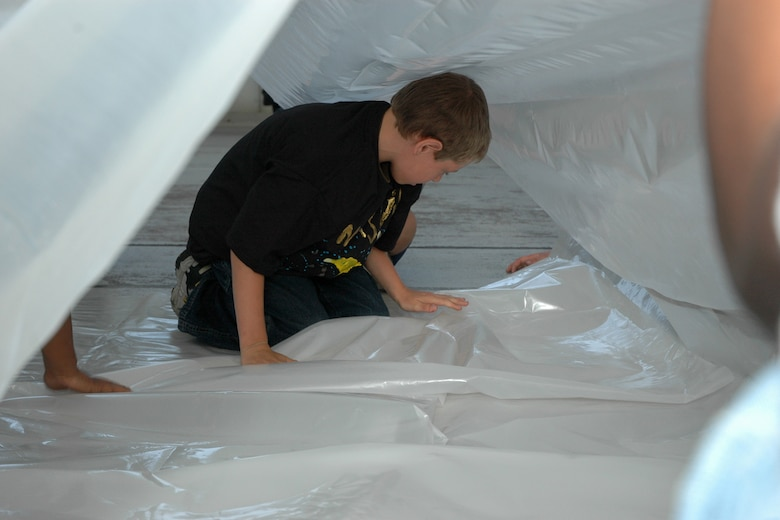 "EGLIN AIR FORCE BASE, Fla. -- Merle Thumma, 11, a fifth grader from Longwood Elementary, folds the plastic shelter into place during Marsville April 20 inside Hangar 110.The folds were in preparation for inflating the plastic shelter. Fifth-grade students from three elementary schools kicked off the Marsville Project culminating six weeks of study about space. The project required students from Cherokee, Valparaiso and Longwood Elementary Schools to experience a day of living in ""space"" by building a habitat. During the weeks prior to Marsville, students learned about the life support systems to consider before travel into space, such as the need for air, water, transportation and garbage disposal. Each student built a life support system model to bring with them. (U.S. Air Force photo by Staff Sgt. Mike Meares)"