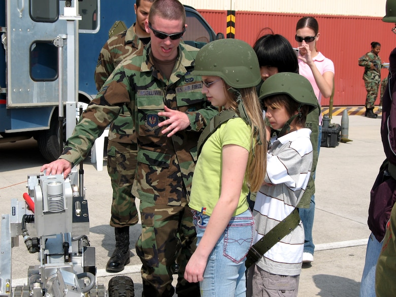 """Airman 1st Class Patrick McGillivray shows """"deployed"""" children the robot they use to diffuse improvised explosive devices in Afghanistan and Iraq during a mock deployment April 20 at Aviano Air Base, Italy. The children got the chance to drive the robot and see how they use the cameras to detect bombs. Airman mcGillivray is assigned to the base's explosive ordnance disposal flight. (U.S. Air Force photo/Airman 1st Class Justin Goodrich)"""