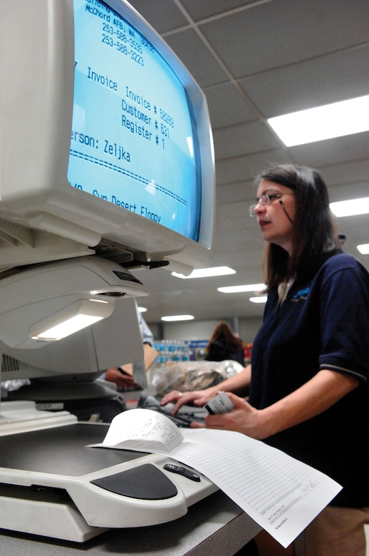 MCCHORD AIR FORCE BASE, Wash. --  Express Store employee Zeljka Harmon, who is legally blind, checks out a customer on April 16 using a product designed to enlarge printed material for people who have low vision and can no longer comfortably use glasses or special lenses to read regular size print. (U.S. Air Force photo/Abner Guzman)