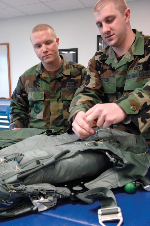 MCCHORD AIR FORCE BASE, Wash. -- Airmen Steven Sontag, left, and Joseph Ripper, both from the 62nd Operations Support Squadron, inspect a parachute  April 16, 2007 in the aircrew life support section warehouse prior to clearing it for pre-positioning aboard an aircraft. (U.S. Air Force photo/Abner Guzman)