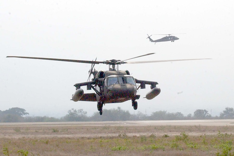 SOTO CANO AIR BASE, REPUBLIC OF HONDURAS -- A 1-228th Aviation Regiment Blackhawk helicopter is marshalled in to the Forward Aerial Refueling Point (FARP) set up this week to train helicopter aircrew and POL Soldiers on proper 'hot' refueling procedures with FARP equipment, while another waits in the background for it's opportunity to refuel. (U.S Air Force photo by Staff Sgt. Chyenne A. Griffin)