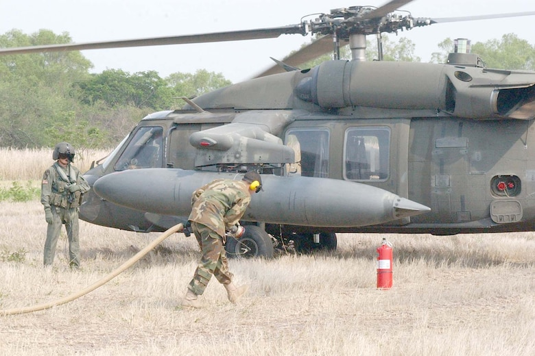 SOTO CANO AIR BASE, REPUBLIC OF HONDURAS -- Army Spc.Gregory Luna, 1-228 Aviation Regiment Petroleum, Oil and Lubricants (POL) section, runs the fuel line out to a waiting Blackhawk helicopter for a 'hot' refuel during Forward Aerial Refueling Point (FARP) training held this week to train POL Soldiers and helicopter aircrew members. (U.S Air Force photo by Staff Sgt. Chyenne A. Griffin)