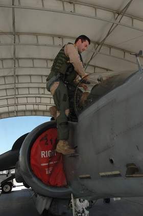 British Royal Air Force Squadron Leader Michael Baker, pilot, Marine Attack Squadron 513, climbs into the cockpit of an AV-8B Harrier jet here Monday. The Harrier is used by Italy, Spain, Britain and the United States.