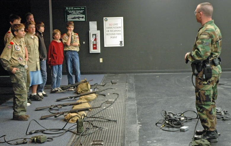 Senior Airman Kevin Gallagher, 90th Security Support Squadron, briefs local Boy Scouts on the different types of weapons and scenarios for the fire arms training system April 14. The Boy Scouts were on a familiarization tour of Warren (Photo by Airman Alex Martinez).