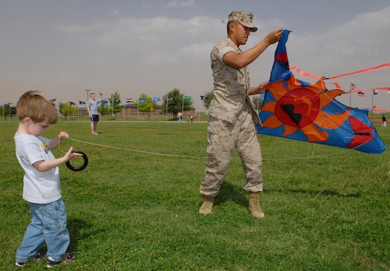 Marine Corps Pfc. Tou Lo (right, with kite) assists 3-year-old Brody Lover with his latest aviation plan during Kite-Flying Day Saturday at the base parade field. (U.S. Air Force photo by Airman 1st Class Kamaile Chan)