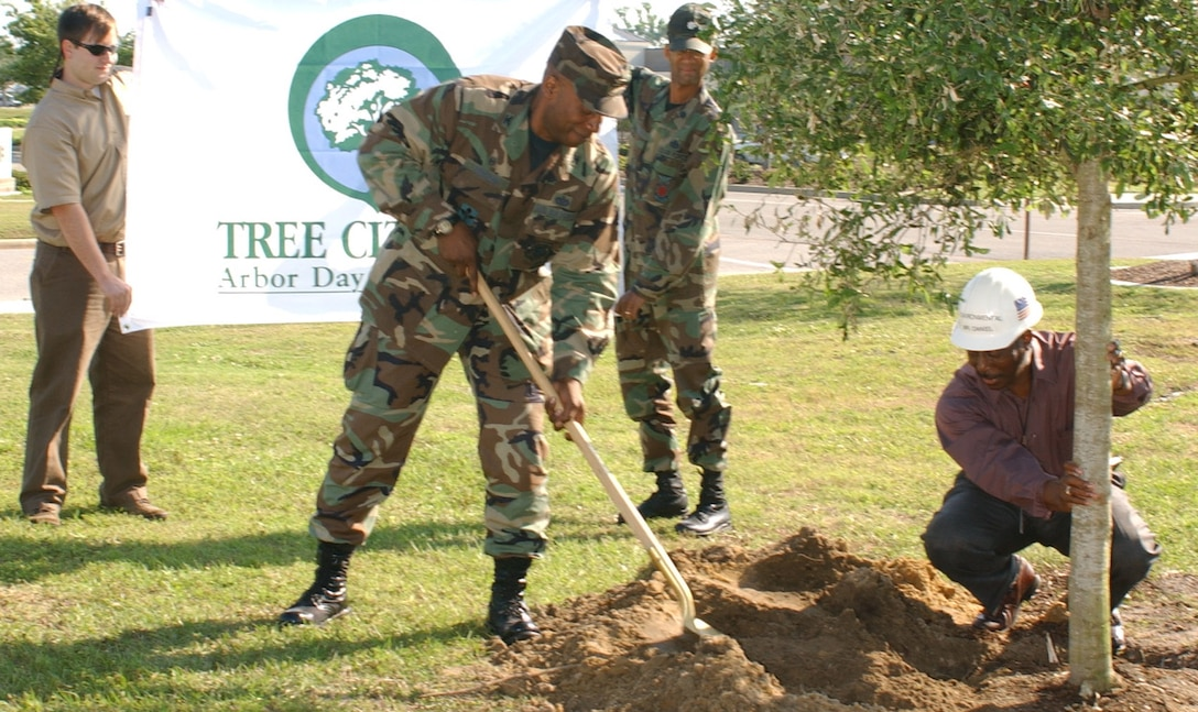 Britt Hubbard, left, Mississippi Forestry Commission, and Lt. Col. Ray Mottley, 81st Civil Engineer Squadron, hold Keesler's Tree City flag as Col. Rodney Croslen, 81st Mission Support Group commander, plants an oak tree held by George Daniel, 81st CES natural/cultural resource manager.  Mr. Hubbard, the commission's Hurricane Katrina urban forest coordinator, recognized Keesler for being named a Tree City for the 14th consecutive year by the National Arbor Day Foundation.  In the past nine months, 2,063 trees have been planted on the main base, equaling the number lost during Hurricane Katrina.  (U.S. air Force photo by Kemberly Groue)