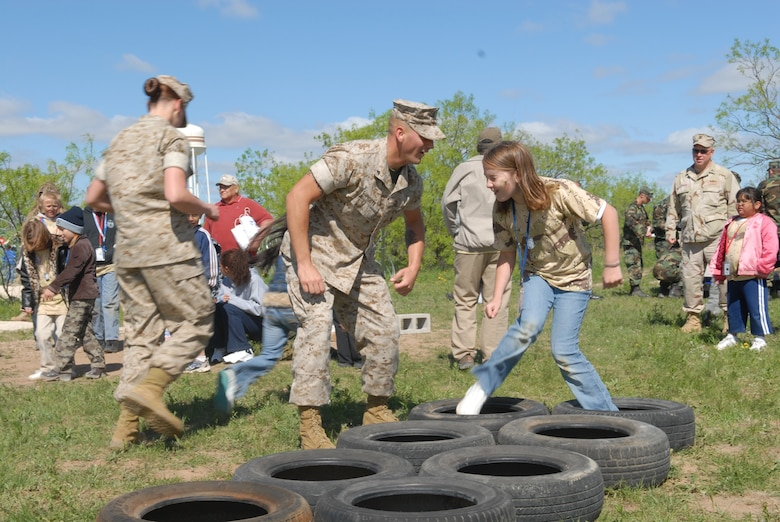 Lance Cpl. William Pigott, an Operation KIDS volunteer assigned to Marine Corps Detachment Goodfellow, motivates Morgan Thrush as she navigates the obstacle course Saturday. The obstacle course was just one of the activities at Discovery Air Base, a mock tent city set up at Goodfellow's Camp Sentinel exercise site. Airmen, Soldiers, Sailors and Marines all volunteered to help with the event. (U.S. Air Force photo by Airman 1st Class Kamaile Chan)