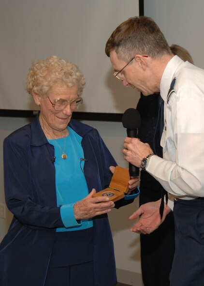 Iris Critchell receives an SMC coin from SMC Vice Commander Brig Gen. Neil McCasland. Mrs. Critchell, began her career in flight in 1939, spoke at LAAFB's Women's History Luncheon, March 28.