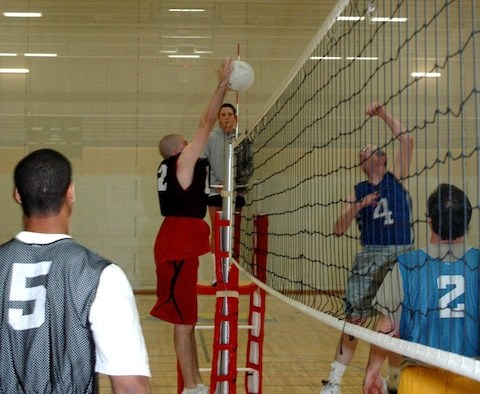 Members from the 28th Communications Squadron take on members from the 28th Munitions Squadron in an intramural volleyball match here at the Bellamy Fitness Center on April 24.  The 28th CS won the match by beating the 28th MUNS in the first 2 games.  (U.S. Air Force photo/Tech. Sgt. Todd Wivell)