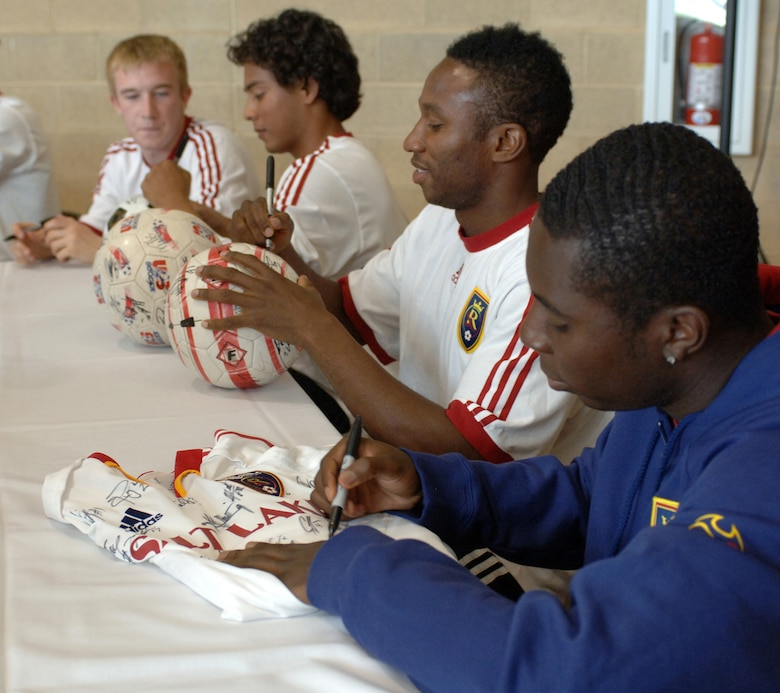 Real Salt Lake player Freddy Adu autographs a shirt while fellow team members (left to right), Christian Jimenez and Jeff Cunningham sign soccer balls for fans during the Salute to Team Hill held at the base fitness center. Photo by Alex R. Lloyd