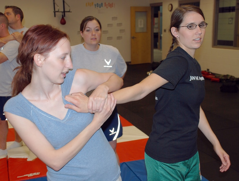 Jessica Lewis, left, performs a self-defense technique on Rachel Wanner, right, April 20, during a women's self-defense class at the fitness center here. Class instructor, Staff Sgt. Kelly Skapik, 22nd Logistics Readiness Squadron, center, watches to ensure the technique is done properly. (Photo by Airman 1st Class Jessica Lockoski)