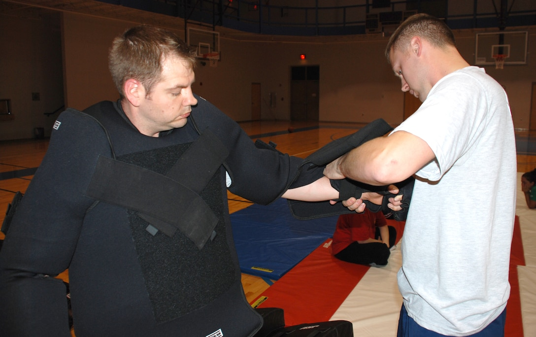 Senior Airman Scott Ury helps Staff Sgt. Sean Gray put on a padded suit, April 18, so he may play the role of an attacker during a women's self-defense course at the fitness center here. Both Airman Ury and Sergeant Gray are members of the 22nd Security Forces Squadron and women's self-defense course instructors. (Photo by Airman 1st Class Jessica Lockoski)