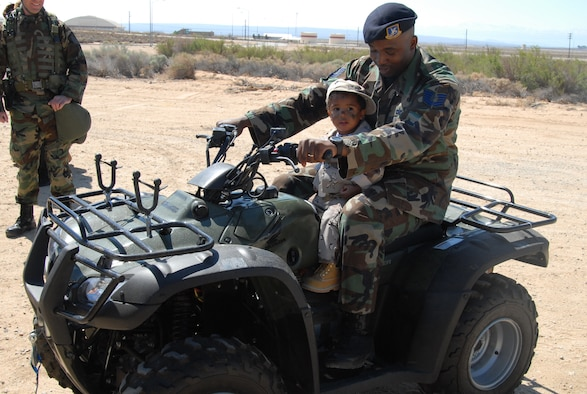 """Tech. Sgt. Robert Tucker, 95th Security Forces Squadron police services noncommissioned officer in charge, assists his 1-year-old son, Christian, on an all-terrain vehicle during Operation KUDOS at the Oasis Community Center on Saturday. Operation KUDOS, or Kids Understanding Deployment Operations, is geared to provide Edwards children the opportunity to process through deployment lines and """"deploy."""" (Photo by Airman Mikeal A. Young)"""