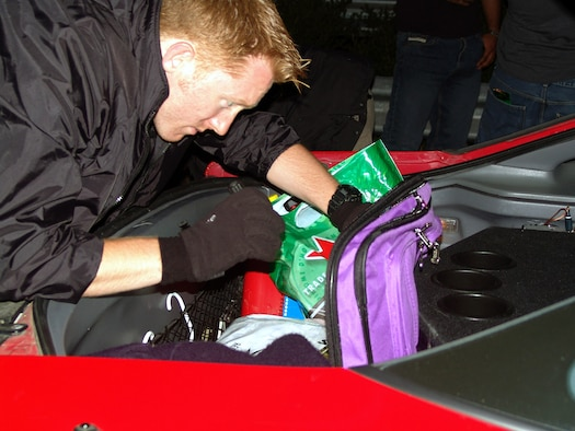 Air Force Office of Special Investigations Special Agent Matthew Mitchell searches the trunk of an American vehicle for illegal substances during a random vehicle check point with German Customs.   Agent Mitchell is assigned to Spangdahlem Air Base, Germany.  (U.S. Air Force photo/Staff Sgt. Jared Frey)