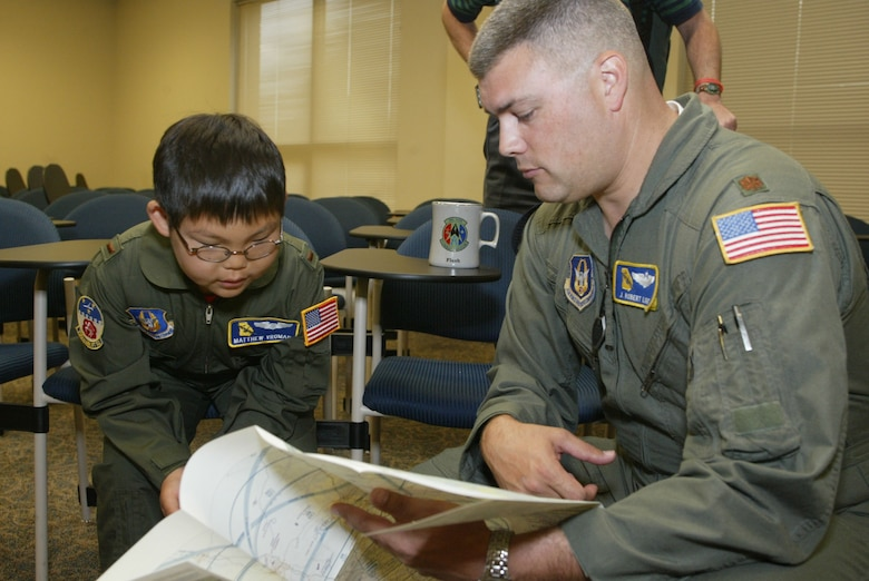 Honorary 2nd Lt. Matthew Vroman reviews a map with Maj. Robert Light as a part of his preflight briefing during a Make-A-Wish event at Dobbins Air Reserve Base, Ga.