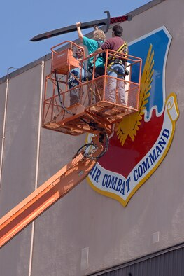 OFFUTT AIR FORCE BASE, Neb. -- Kay Barbara (center), a sign painter from the 55th Civil Engineer Squadron, assists John Abbod (right) and Ron Mona (left), 55th CES maintenance workers, in installing the sword on a new, freshly painted Air Combat Command Shield on Bldg. 305 April 18. (U.S. Air Force Photo by Josh Plueger)