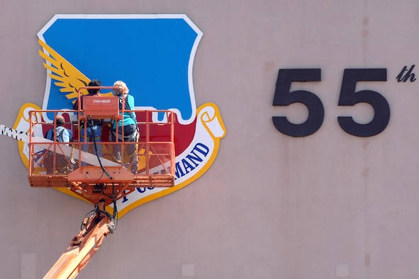 OFFUTT AIR FORCE BASE, Neb. -- Kay Barbara (right), a sign painter from the 55th Civil Engineer Squadron, assists John Abbod (middle) and Ron Mona (left), 55th CES maintenance workers, in installing the wings on a new, freshly painted Air Combat Command Shield on Bldg. 305 April 18. (U.S. Air Force Photo by Josh Plueger)