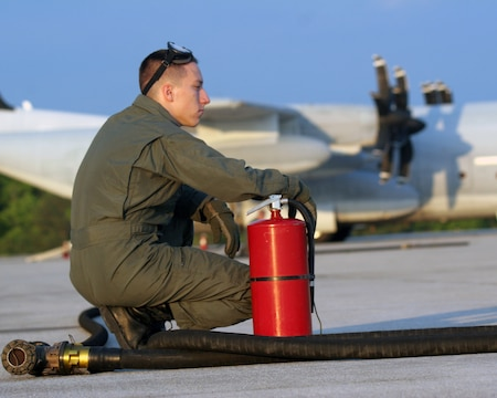 Lance Cpl. Anthony Abel, a loadmaster with Marine Aerial Refueling Transport Squadron 252, waits by the fire extinguisher during a Rapid Ground Refueling mission at Blackstone Army Air Field, near Fort Pickett, Va., April 28, 2007. Abel will be the first line of defense in case of a fire during the refueling process. Abel and the rest of his crew were refueling humvees and Light Armored Vehicles from Light Armored Reconnaissance Platoon, Weapons Company, Battalion Landing Team, 3rd Battalion, 8th Marine Regiment, 22nd Marine Expeditionary Unit. The Marines and Sailors of BLT 3/8 are scheduled to deploy as the Ground Combat Element of the 22nd Marine Expeditionary Unit later this year. (Official Marine Corps photo by Sgt. Ezekiel R. Kitandwe)