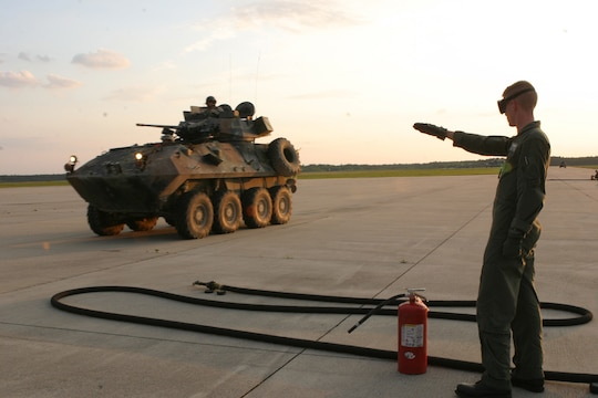 Lance Cpl. John Busclas, a loadmaster with Marine Aerial Refueling Transport Squadron 252, directs a Light Armored Vehicle (LAV) to a Rapid Ground Refueling point at Blackstone Army Air Field, near Fort Pickett, Va., April 28, 2007. The LAV is with Light Armored Reconnaissance Platoon, Weapons Company, Battalion Landing Team, 3rd Battalion, 8th Marine Regiment, 22nd Marine Expeditionary Unit. The Marines and Sailors of BLT 3/8 are scheduled to deploy as the Ground Combat Element of the 22nd Marine Expeditionary Unit later this year. (Official Marine Corps photo by Sgt. Matt Epright)