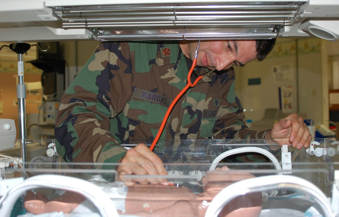 Major Vargas simulates checking a newborn's vitals in one of the NICU's state-of-the-art Versalets, using a training mannequin.  The Versalet can serve as an isolet or a baby warmer.  (U.S. Air Force photo by Steve Pivnick)