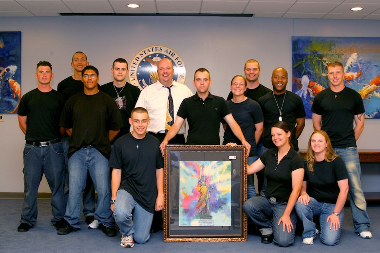 Scott Sedgwick, Artsouth Productions, and volunteer technical training students take a group photo after the Keeser Spouse's Club Art Auction April 28 at the Levitow Training Support Facility.  The auction raised $3,000 for scholarships awarded to students and spouses of personnel affiliated with Keesler to include active-duty military, retired military, active-duty reserve, military deceased, and DoD civilian employees. The scholarships will be awarded May 15 at the Vandenberg Community Center from 5:30 p.m. to 6:30 p.m. (U.S. Air Force Photo by Major Aldwin Estrellado)