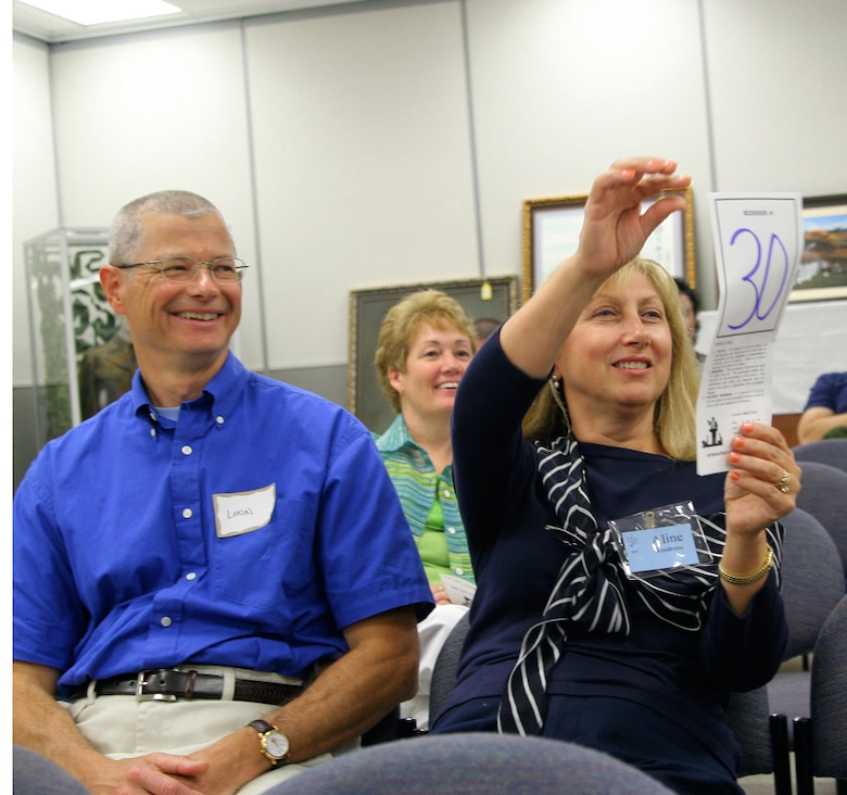 Col. Leon Kundrotas, 81st Medical Operation Squadron, and his wife Aline, place a bid on a piece of art using their auction paddle at the Keesler Spouse's Club Art Auction, which was held April 28 at the Levitow Support Facility.  The auction raised $3,000 for scholarships.  The scholarships are awarded to students and spouses of personnel affiliated with Keesler to include active-duty military, retired military, active-duty reserve, military deceased, and DoD civilian employees. The scholarships will be awarded May 15 at the Vandenberg Community Center from 5:30 p.m to 6:30 p.m. (U. S. Air Force Photo by Major Aldwin Estrellado)