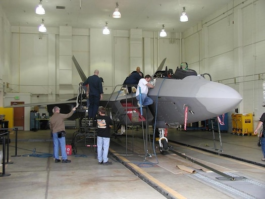 Cutline: Mechanics from the 309th Aircraft Maintenance Group F-22 Division install the Night Air-to-Air Refueling modification on an F-22. Courtesy photo