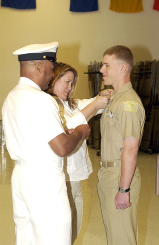Carole Glovak pins chief petty officer insignia on her son Cody Blackshears collar assisted by Senior Chief Petty Officer Craig Cook.  Cody was being promoted to chief petty officer within the U.S. Naval Sea Cadet Corps, located at March Air Reserve Base. (U.S. Air Force photo by SSgt Amy Abbott, 452 AMW/PA)
