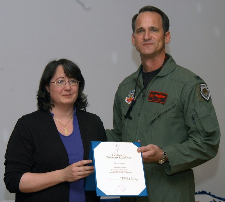 Angellina Ribordy accepts the Volunteer Excellence Award from Col. Jim Jones, 55th Wing Commander, for 18 years of service as a Girl Scout volunteer. Offutt's National Volunteer Week recognition ceremony was held April 19 at the Patriot Club. (U.S. Air Force Photo by Jeff Gates)