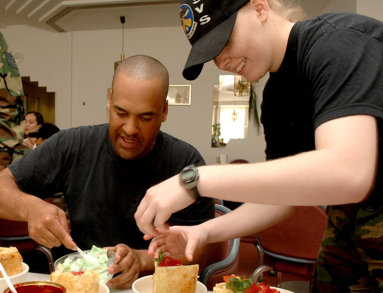 SPANGDAHLEM AIR BASE, GERMANY -- Master Sgt. Andre Tolliver and Airman 1st Class Brandi Clemons, both from the 52nd Services Squadron,  put the final touches on their cherry ice cream turnovers during the Iron Chef competition test run at the Mosel Dining Facility. (US Air Force photo/Senior Airman Josie Kemp)