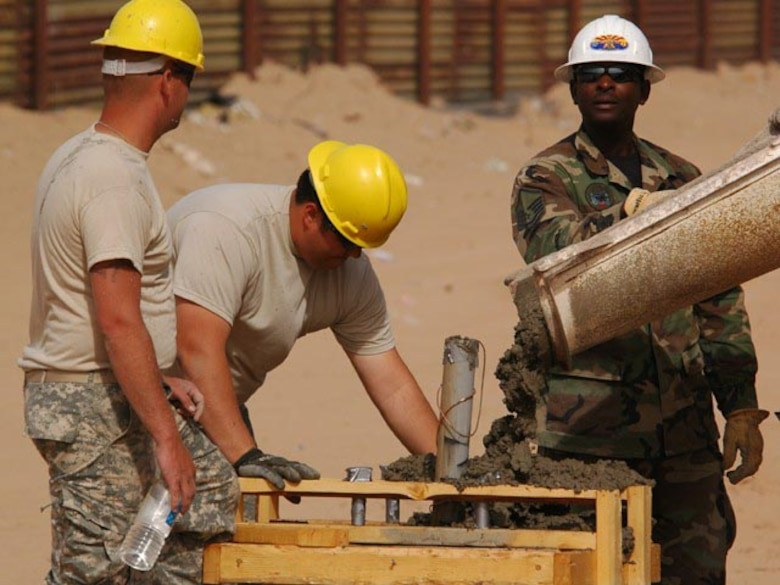 Master Sgt. Darryl S. Ennels, of the 175th Civil Engineer Squadron, in the green battle dress uniform, directs concrete pouring into forms used to create bases for light poles which are positioned between the primary and secondary fences along the Arizona-Mexico border, June 6, 2007.  Two members of the North Dakota Army National Guard 188th Engineer Company are troweling the concrete as it fills the form.  The joint force mission of Task Force Diamondback, under Operation JUMP START, is to erect and reinforce segments of border fence and to construct obstacles along the border to help secure the southwest U.S.-Mexico border.  (USAF photo/Senior Master Sgt. David H. Lipp)