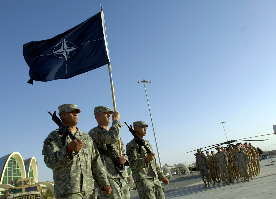 Staff Sgt. Gilbert Gonzalez, Staff Sgt. Christopher Lilly, and Tech. Sgt. Jimmy Tron secure the NATO flag at Kandahar Air Field, Afghanistan, July 31, during a historic change-of-command ceremony that culminated a year-long effort to bring Kandahar under NATO control.  The ceremony marked the first time NATO has taken full control of a large airfield and operational staging base in an active operational theater using a multi-national team.  The three Airmen are deployed from the 48th Security Forces Squadron, Royal Air Force Lakenheath, United Kingdom. (U.S. Air Force photo/Master Sgt. Jim Varhegyi)