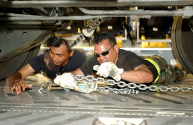 Senior Airman Frederick Eleazar and Senior Airman Kyle Orian, 50th Aerial Port Squadron, tighten down chains to secure a 60k Tunner on a  C-17 Globemaster III at March during Patriot Hook. U.S. Air Force photo by Senior Airman Sarah N. Sutliff